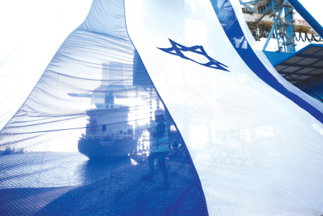 A WORKER at the sea port of Ashdod coordinates a crane to hang a giant Israeli national flag ahead of Remembrance Day.