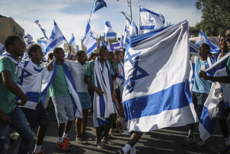 Groups of Jewish youth movements wave Israeli flags as they celebrate Jerusalem Day by the Great Synagogue, on King George Street, before taking part in the parade to the Old City. Jerusalem Day celebrates the 47th anniversary of its capture of Arab East Jerusalem in the Six Day War of 1967.