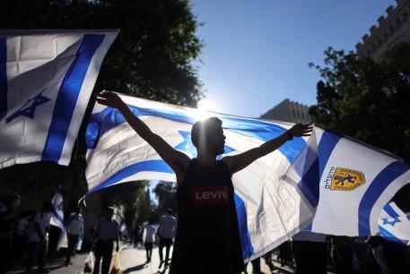 An Israeli man holds an Israeli flag outside Jerusalem's Old City