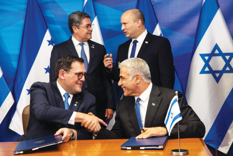 Prime Minister Naftali Bennett stands next to Honduran President Juan Orlando Hernandez, as Honduran Foreign Minister Lisandro Rosales and Foreign Minister Yair Lapid sign agreements at the Prime Minister's Office in Jerusalem yesterday.