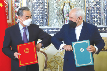IRAN'S FOREIGN MINISTER Mohammad Javad Zarif and China's Foreign Minister Wang Yi bump elbows during the signing ceremony of a 25-year cooperation agreement, in Tehran, in March.