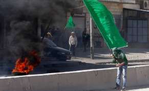 A Palestinian protester holds a Hamas flag during clashes with Israeli troops in the West Bank