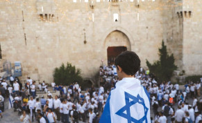 A BOY wrapped with Israel's national flag is seen during a parade marking Jerusalem Day last month outside the Old City Walls. Israel, the author argues, needs to assert more sovereignty