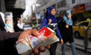 Palestinian women walk past a money changer in the West Bank city of Ramallah February 16, 2010. REUTERS/Mohamad Torokman/File Photo
