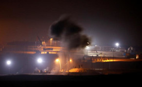 Smoke rises after an explosion as Palestinians take part in a night protest held along the Gaza side of the border with Israel