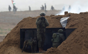 Israeli soldiers wait in position near the border fence between Israel and the Gaza Strip, during a protest on the Gaza side, as seen from the Israeli side March 30, 2019