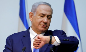 Israeli Prime Minister Benjamin Netanyahu looks at his watch before delivering a statement at the Knesset, Israel's parliament,