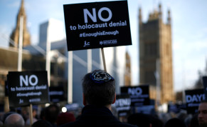Protesters hold placards and flags during a demonstration, organised by the British Board of Jewish Deputies for those who oppose antisemitism, in Parliament Square in London