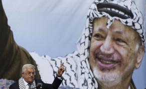 Palestinian President Mahmoud Abbas gestures beneath a poster of the late Palestinian leader Yasser Arafat