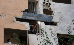 A worker fixes the damage to a building from an Israeli attack in Damascus, Syria November 20, 2019.