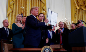White House senior advisors Ivanka Trump and Jared Kushner, New England Patriots owner Robert Kraft and others stand behind U.S. President Donald Trump as he holds up an executive order on anti-semitism that he signed during a Hanukkah reception in the East Room of the White House in Washington, U.S