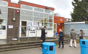 VOTERS AND TELLERS outside of polling station inside Menorah Primary School in Golders Green, London