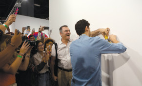 A worker attaches a banana to the wall with duct tape where the artwork 'Comedian' by the artist Maurizio Cattelan was exhibited in Miami Beach Florida last week.