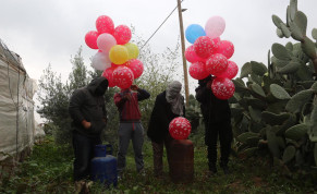 Masked Palestinians release incendiary balloons near Khan Yunis in the Gaza Strip