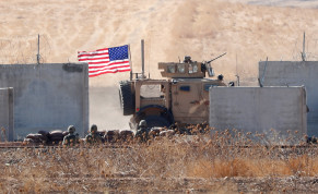 A US military vehicle is pictured behind the Turkish border walls during a joint US-Turkey patrol in northern Syria, 2019