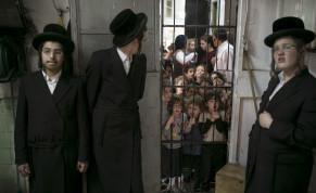 Schoolchildren stand in the doorway and watch as ultra-Orthodox Jews prepare matza in Bnei Brak near Tel Aviv March 30, 2015.