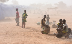 Displaced people, who fled from attacks of armed militants in Roffenega, are engulfed in dust as they sit at the camp built by the German Ngo HELP in Pissila