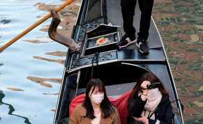 Tourists wearing protective masks travel on a gondola in Venice, Italy, February 7, 2020.