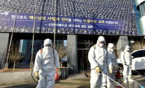 """Workers from a disinfection service company sanitize a street in front of a branch of the Shincheonji Church of Jesus the Temple of the Tabernacle of the Testimony where a woman known as """"Patient 31"""" attended a service in Daegu, South Korea, February 19, 2020"""