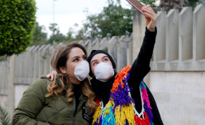 People wearing face masks take a picture with a mobile phone outside Rafik Hariri hospital, where Lebanon's first coronavirus case is being quarantined, in Beirut