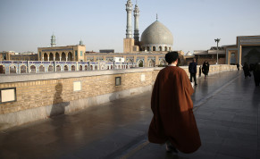 An Iranian cleric walks in front of the Shrine of Fatima Masumeh in Qom