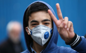 An Iranian boy gestures as he wears protective mask to prevent contracting a coronavirus in Tehran