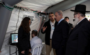 Israeli Prime Minister Benjamin Netanyahu arrives to a tent during his visit to the Chaim Sheba Medical Center at Tel Hashomer in Ramat Gan, Israel, for discussion on the coronavirus, February 19, 2020