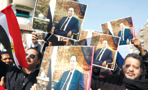 SUPPORTERS OF former Egyptian president Hosni Mubarak hold his photos near the main gate of a cemetery during his funeral ceremony, east of Cairo.