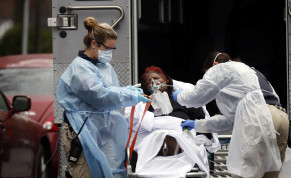 Emergency Medical Technicians wearing protective gear wheel a sick patient to a waiting ambulance during the outbreak of coronavirus disease in New York City, March 28, 2020