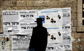 A Jewish ultra-Orthodox man looks onto a local billboard with instructions related to the coronavirus at a street in a Jewish Orthodox neighborhood in Jerusalem, March 27, 2020