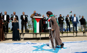 A Palestinian woman steps on a replica of an Israeli flag during an event marking Land Day near the Israel-Gaza border as mass rallies planned to commemorate the event were cancelled amid concerns about the spread of coronavirus, east of Gaza City March 30, 2020