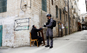 An ultra-Orthodox Jewish man speaks to an Israeli policeman after police removed him from a synagogue before closing it as they enforce restrictions of a partial lockdown against the coronavirus disease (COVID-19) in Mea Shearim neighbourhood of Jerusalem March 30, 2020.