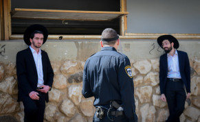 Israeli police officers take out Ultra orthodox jewish men from the Ponevezh Yeshiva in Bnei Brak, as part of an effort to enforce lockdown in order to prevent the spread of the Coronavirus, April 2, 2020.