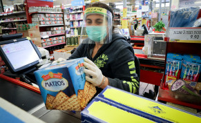 People wear face masks to protect them from the coronavirus as they buy matzot, unleavened bread traditionally eaten during the Jewish holiday of Passover, at a supermarket in Jerusalem. March 31, 2020.