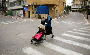 """An ultra-Orthodox Jewish woman crosses a street with her children in Bnei Brak, a town badly affected by the coronavirus disease (COVID-19), and which Israel declared a """"restricted zone"""" due to its high rate of infections, near Tel Aviv, Israel April 5, 2020"""