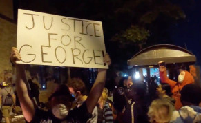 A demonstrator holds a placard while protesters gather around an on fire entrance of a police station, as demonstrations continue after a white police officer was caught on a bystander's video pressing his knee into the neck of African-American man George Floyd, who later died at a hospital, in Minn