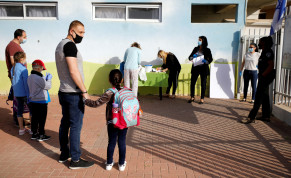 FILE PHOTO: Parents wait with their children to enter their elementary school in Sderot as it reopens following the ease of restrictions preventing the spread of the coronavirus disease (COVID-19) in Israel May 3, 2020