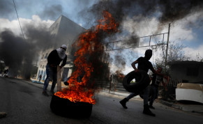 A demonstrator moves a tire during an anti-Israel protest following the funeral of Palestinian man Ibraheem Yakoub, in Kifl Haris in the West Bank July 10, 2020