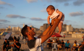 A Palestinian man lifts up his niece on a beach after the coronavirus disease (COVID-19) restrictions were largely eased, in Gaza City July 17, 2020.