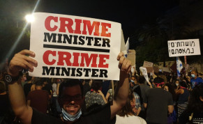 "Protester holds a sign that says ""crime minister"" outside of the Prime Minister's Residence during a demonstration on July 25, 2020"
