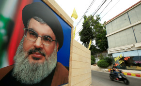 A man rides a motorbike past a picture of Lebanon's Hezbollah leader Sayyed Hassan Nasrallah, near Sidon.