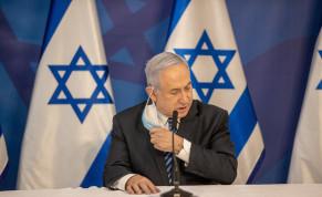 Prime Minister Benjamin Netanyahu removing his mask