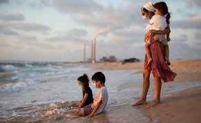 Children wearing masks play in the water along the shore of the Mediterranean Sea as they visit Zikim beach, amid the coronavirus disease (COVID-19) outbreak, in southern Israel July 21, 2020
