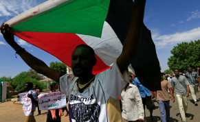 A Sudanese protester carries their national flag as they march in a demonstration to mark the anniversary of a transitional power-sharing deal with demands for quicker political reforms in Khartoum, Sudan August 17, 2020