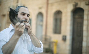 AN ULTRA-ORTHODOX man watches protesters march across Jerusalem's 'Bridge of Strings' in August.