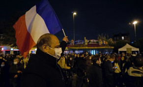 A man waves a French national flag during a silent march to pay tribute to Samuel Paty, the French teacher who was beheaded on the streets of the Paris suburb of Conflans-Sainte-Honorine, France, October 20, 2020