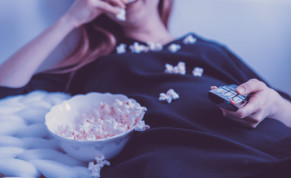 A woman eats popcorn while watching television.