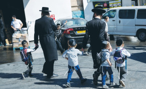 A FATHER walks his children home from school in Jerusalem on Sunday.