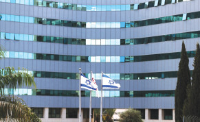 Israeli national flags flutter in front of an office tower at a business park housing high tech companies, at Ofer Park in Petah Tikva.