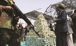 HOUTHI FOLLOWERS stand by bills of Yemeni currency during a ceremony in Sana'a in September 2020 to collect supplies for their fighters battling government forces.